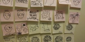 "A wall covered in sticky notes with drawings used in the stop-motion video ""Ombre"""